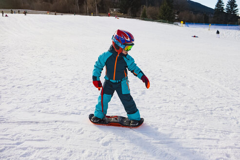 Italy, Trentino-Alto Adige, boy riding on small snowboard on piste - MGIF00326