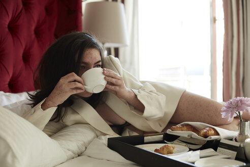 Teenage girl having breakfast in bed - AMEF00016