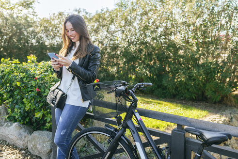 Smiling young woman with bicycle in park using cell phone - KIJF02362