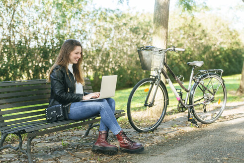 Young woman sitting on a bench in park using laptop - KIJF02371