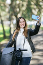 Smiling young woman with bicycle in park taking a selfie - KIJF02374