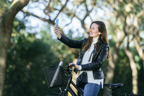 Smiling young woman with bicycle in park taking a selfie - KIJF02380