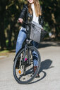 Low section of young woman with bicycle on park way - KIJF02383