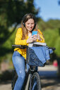 Smiling young woman with bicycle, headphones  and cell phone - KIJF02386