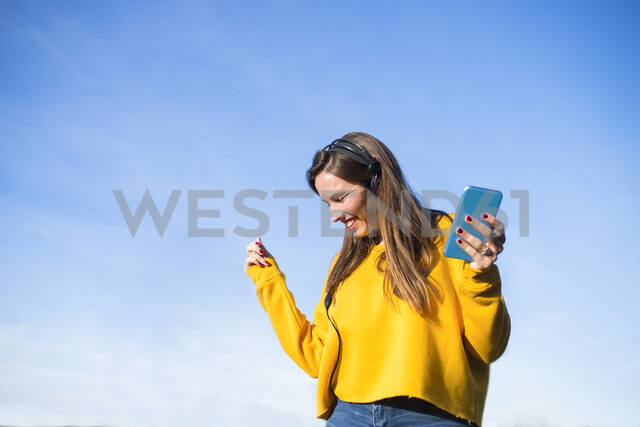 Happy young woman with cell phone listening to music with headphones - KIJF02389 - Kiko Jimenez/Westend61