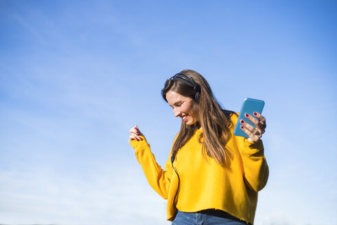 Happy young woman with cell phone listening to music with headphones - KIJF02389