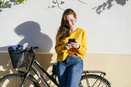 Smiling young woman with bicycle using cell phone at a wall - KIJF02392