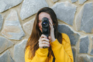 Young woman with vintage camera at a stone wall - KIJF02398