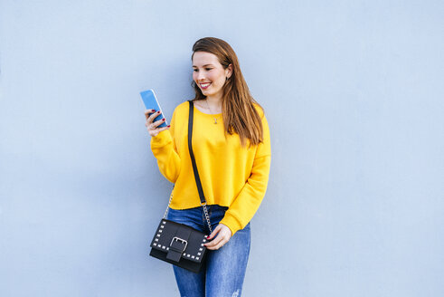 Smiling young woman standing at a wall using cell phone - KIJF02401