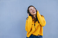 Happy young woman listening to music with headphones at blue wall - KIJF02407