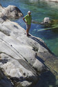 Switzerland, Ticino, Verzasca Valley, man standing on rock at clear turquoise waters of Verzasca river - GWF05952