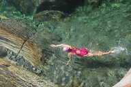 Switzerland, Ticino, Verzasca Valley, woman swimming in refreshing Verszasca river - GWF05955
