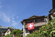 Switzerland, Ticino, Sonogno, typical historic stone house with Swiss Flag - GWF05976