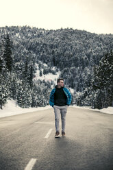 Young man walking on a snowy road with trees in the background - ACPF00480