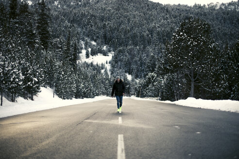Young man walking on a snowy road with trees in the background - ACPF00486