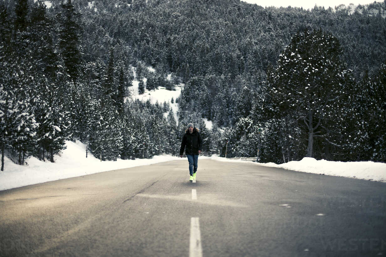Young man walking on a snowy road with trees in the background - ACPF00486 - Aitor Carrera Porté/Westend61
