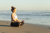 Woman meditating on the beach in the evening - KBF00537