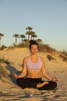 Woman meditating on the beach in the evening - KBF00540