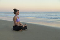 Woman meditating on the beach in the evening - KBF00546