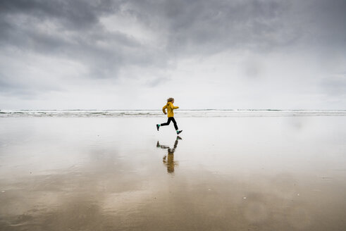 Side view of boy running at beach against cloudy sky - CAVF62328
