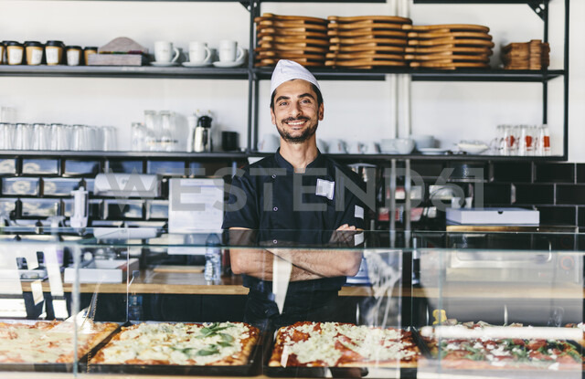 Portrait of smiling chef with arms crossed standing by retail display in pizzeria - CAVF62352