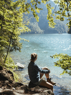 Side view of woman looking at lake while sitting on rocks in forest during sunny day - CAVF62364