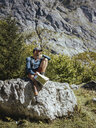 Full length of hiker with map sitting on rock against mountain in forest during sunny day - CAVF62373