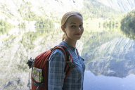Portrait of smiling female backpacker standing by lake against mountains in forest - CAVF62376