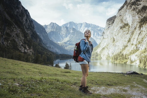 Full length of female backpacker looking at view by lake and mountains in forest - CAVF62379