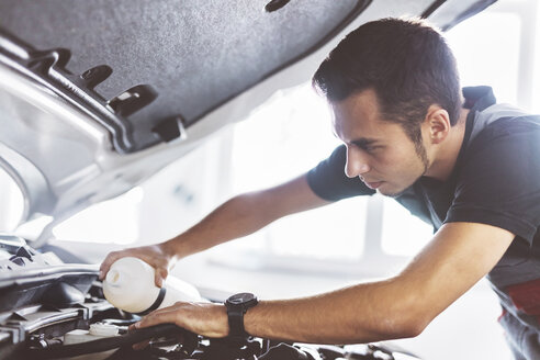 Maintenance engineer doing car oil change at auto repair shop - CAVF62412
