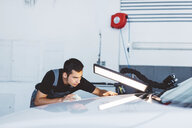 Engineer examining car hood by illuminated lamp while working in auto repair shop - CAVF62415