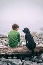 Boy and dog enjoying seaside - CUF49449
