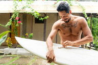 Man preparing surfboard, Pagudpud, Ilocos Norte, Philippines - CUF49506