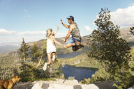 Side view of happy couple jumping on mountain against sky in forest - CAVF62446