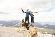 Portrait of couple with dogs standing on mountain against cloudy sky - CAVF62449