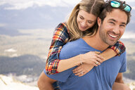 Portrait of happy boyfriend piggybacking girlfriend while standing on mountain - CAVF62452