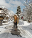 Full length of young woman wearing warm clothing standing on road during winter - CAVF62512