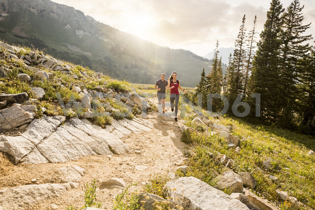 Couple running on mountain against cloudy sky during sunny day - CAVF62521 - Cavan Images/Westend61