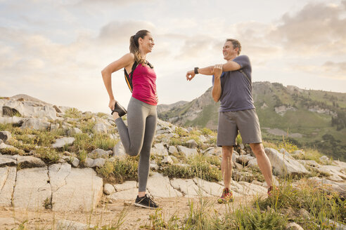Low angle view of smiling couple exercising while standing on mountain against sky in forest - CAVF62524