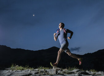 Low angle view of confident male hiker running on mountain against blue sky at night - CAVF62527