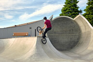 Rear view of rider with BMX bike jumping on concrete ramp against sky at skateboard park - CAVF62563