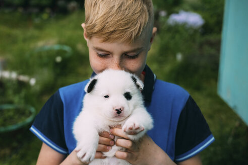 Close-up of boy carrying cute puppy while standing in yard - CAVF62590