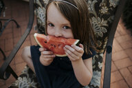 High angle portrait of cute girl eating watermelon while sitting on chair in yard - CAVF62605