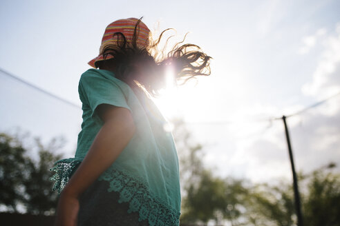 Low angle view of girl wearing hat enjoying in trampoline against sky during sunny day - CAVF62617