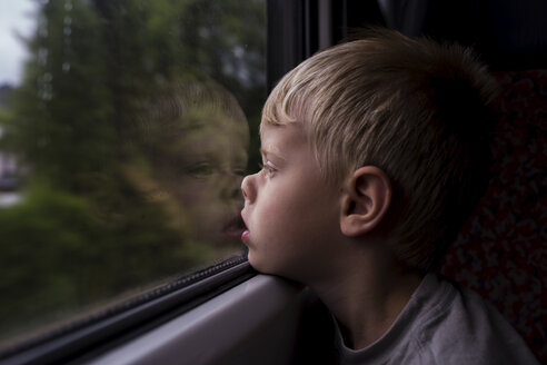 Side view of thoughtful boy looking through window while traveling in train - CAVF62626