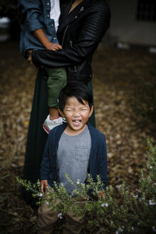 Baby boy crying while mother carrying son on grassy field at Balboa Park - CAVF62641