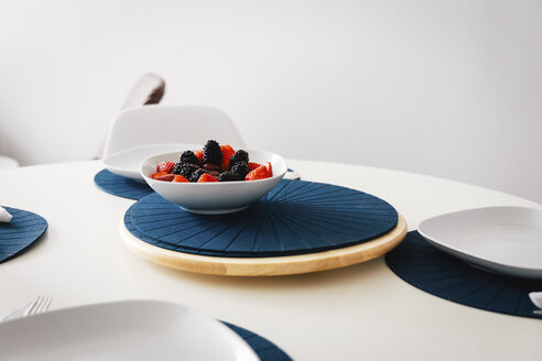 Berry fruits in bowl on table against wall at home - CAVF62668
