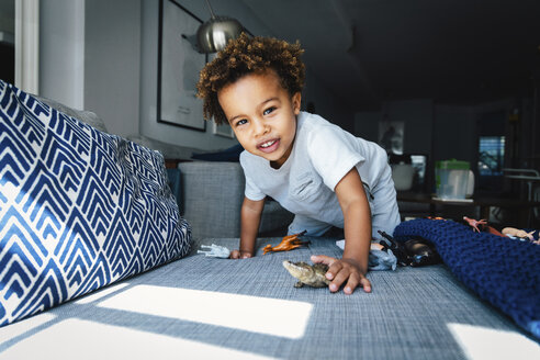 Portrait of cute boy playing with toys on sofa at home - CAVF62671