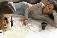Friends putting pins on a map, planning their vacations - FMOF00423