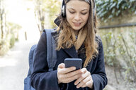 Young woman with headphones, using smartphone, walking in the city - FMOF00432